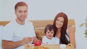 Família de sorriso que come o pequeno almoço foto de stock
