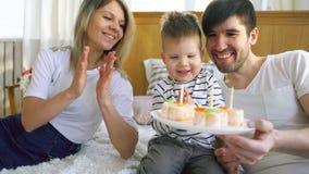 Família de sorriso que comemora seu aniversário do filho junto antes de fundir velas no bolo fotos de stock