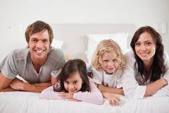 Família de sorriso que encontra-se em uma cama Fotos de Stock
