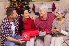 Família de sorriso que guarda atual no sofá Foto de Stock Royalty Free