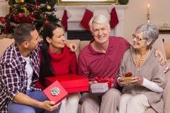 Família de sorriso que guarda o presente no sofá Imagem de Stock