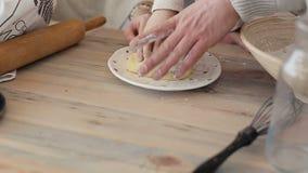 Família de sorriso que joga com farinha da cookie no contador de cozinha ao fazer cookies do Natal Cookies e queques cozidos sobr video estoque
