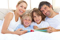 Família de sorriso que lê um livro na cama fotografia de stock