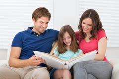 Família de sorriso que olha o álbum de fotografias fotografia de stock royalty free
