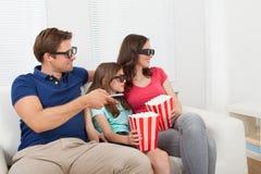 Família de sorriso que olha o filme 3d em casa Fotografia de Stock Royalty Free