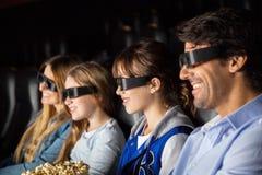 Família de sorriso que olha o filme 3D no teatro Imagem de Stock