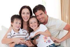Família de sorriso que presta atenção à tevê na sala de visitas Fotografia de Stock Royalty Free