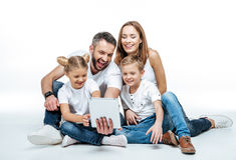 Família de sorriso que usa a tabuleta digital imagem de stock