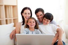 Família de sorriso que usa um portátil no sofá Foto de Stock