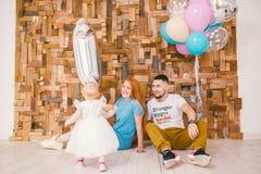 A família de três comemora o aniversário do ` s da filha um ano dentro da sala que senta-se no assoalho na perspectiva do de made foto de stock