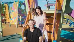 Família de três feliz que sentam-se na corrediça do ` s das crianças no campo de jogos filme