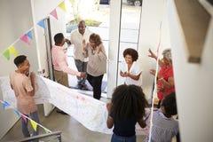 Família de três gerações convidados de acolhimento de jogo do partido de surpresa na porta da rua, vista elevado imagens de stock royalty free