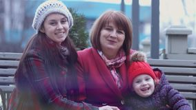 Família de três gerações de mulheres de sorriso que sentam-se em um banco no parque da cidade e que guardam as mãos Conceito de f video estoque