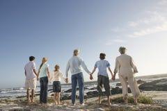 Família de três gerações que guarda as mãos no litoral Fotografia de Stock