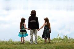 Família de três miúdos e de lago Fotografia de Stock Royalty Free