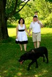 Família de três nova que anda com cão Imagem de Stock Royalty Free