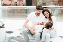A família de três, o pai, a mãe e a filha estão sentando-se no banco no shopping foto de stock