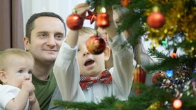 A família decora junto a árvore de Natal, o bebê, o irmão e os pais novos, celebração da alegria filme