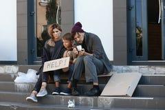 Família desabrigada pobre que implora e que pede a ajuda foto de stock