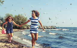 Família despreocupada feliz que corre na praia no mar Fotografia de Stock
