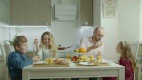 Família despreocupada que tem o divertimento durante o café da manhã filme