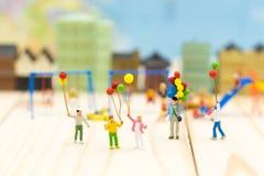 Família diminuta: Balão da terra arrendada das crianças que joga junto Im fotos de stock