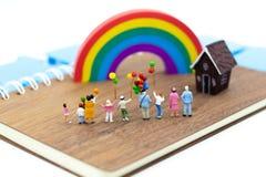 Família diminuta: O balão de jogo das crianças junto Uso da imagem para o dia internacional do fundo do conceito de famílias fotografia de stock