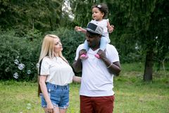 Família diversa feliz com a filha no parque A família inter-racial feliz está fundindo bolhas imagens de stock