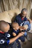 Família do African-American que presta atenção à tevê com o telecontrole da terra arrendada do menino. Imagens de Stock Royalty Free