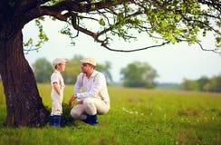 Família do fazendeiro que tem o divertimento sob uma árvore velha, campo da mola Fotos de Stock