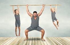 Família do homem forte Gene e dois filhos no arrasto dos trajes do vintage a corda Olhar da família fotos de stock royalty free