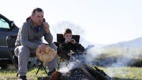 Família do pai e do filho que comem o pão roasted ao lado da fogueira vídeos de arquivo