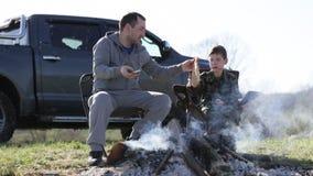 Família do pai e do filho que comem o pão roasted ao lado da fogueira filme