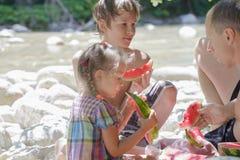 Família do piquenique da praia do três com melancia fotografia de stock royalty free