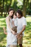 A família docemente bonita está relaxando no parque A mamã e o paizinho estão guardando a filha nos braços e estão abraçando seu  imagens de stock royalty free