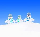 Família dos bonecos de neve em lenços feitos malha na neve do inverno contra o céu Imagens de Stock Royalty Free