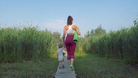 Família dos esportes, mãe nova dos esportes com caminhadas da criança pequena na ponte na natureza entre a vegetação verde após p