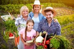 Família dos fazendeiros que guarda vegetais do jardim fotografia de stock