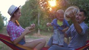 Família dos jardineiro, do mum novo e do paizinho jogando com os chapéus de palha com a criança bonito no pomar na luz solar vídeos de arquivo