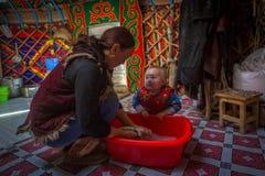 Família dos Kazakhs dos caçadores com caça do interior das águias douradas seu o mongolian Yurts foto de stock royalty free
