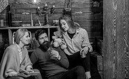 Família dos leitores ávidos que leem junto no sofá Pais e Natal da despesa da filha adolescente no campo bearded imagem de stock royalty free