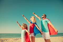 Família dos super-herói na praia Conceito das férias de verão fotos de stock royalty free