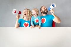 Família dos super-herói que jogam em casa foto de stock