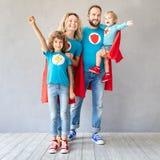 Família dos super-herói que jogam em casa imagens de stock