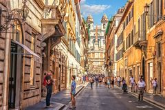 Família dos turistas dentro através do dei Condotti, de uma rua que conduzem a Praça di Spagna e das etapas espanholas imagem de stock