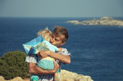 Família dos viajantes O pai que abraça e beija seu filho da criança ao estar na borda do litoral rochoso, com mapa do turista den imagem de stock royalty free