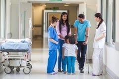 Família, doutor e enfermeira indianos asiáticos no corredor do hospital
