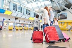 A família e as crianças no aeroporto estão esperando a partida foto de stock