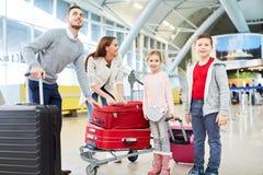 Família e duas crianças com bagagem no terminal imagens de stock royalty free