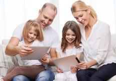 Família e duas crianças com os computadores do PC da tabuleta Foto de Stock